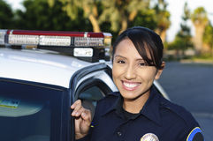 Police officer. A Hispanic female police officer smiling and standing next to her unit Stock Images