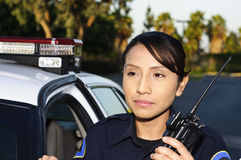 Police officer. A Hispanic female police officer smiling and standing next to her unit Stock Photography