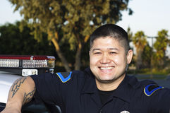 Police officer. A smiling police officer standing next to his car Royalty Free Stock Images