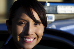 Police officer. A female Hispanic officer smiling while standing next to her police car Royalty Free Stock Photos