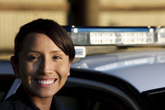Police officer. A female Hispanic officer smiling while standing next to her police car Royalty Free Stock Photography