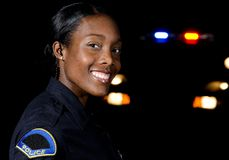 Police officer. A female police officer in the night during her shift with her patrol car in the background Royalty Free Stock Image