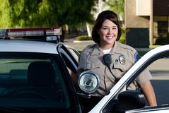 Police officer. A friendly looking police officer smiles and stands next to her patrol car Stock Image