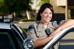 Police officer. A friendly looking police officer smiles and stands next to her patrol car Stock Photography