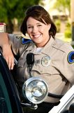 Police officer. A friendly looking police officer smiles and stands next to her patrol car Stock Photo