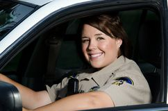 Police officer. A friendly looking female police officer sits and smiles in her patrol car Royalty Free Stock Image
