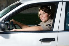 Police officer. A friendly looking female police officer sits and smiles in her patrol car Stock Image
