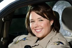 Police officer. A friendly looking female police officer sits and smiles in her patrol car Stock Photos