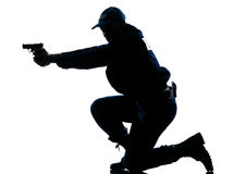 Police officer aiming gun. Side view of a silhouetted Afro American police officer aiming gun isolated on white background Royalty Free Stock Photos