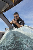Police Officer Aiming Gun Through Broken Windshield Stock Image