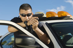 Police Officer Aiming Handgun. Police officer aiming with handgun by patrol car Royalty Free Stock Photos