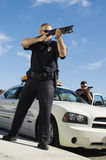 Police Officer Aiming Shotgun. Police officers aiming shotgun by patrol car Royalty Free Stock Image