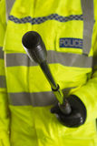 Police officer with baton. Police officer wearing fluorescent jacket with police label, pointing a baton to the camera Royalty Free Stock Photography