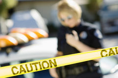 Police Officer Behind Caution Tape. Closeup of yellow caution tape with female police officer in the background royalty free stock photo