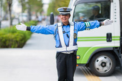 Police officer is blocking the pedestrian crossing for municipal truck. Tokyo, Japan Royalty Free Stock Photos