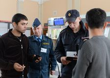 A police officer checks documents from citizens at the railway station of Tula station. TULA, RUSSIA - SEPTEMBER 30, 2015: A police officer checks documents Royalty Free Stock Images