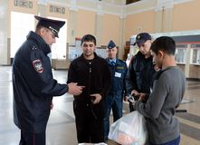 A police officer checks documents from citizens at the railway station of Tula station. TULA, RUSSIA - SEPTEMBER 30, 2015: A police officer checks documents Royalty Free Stock Image