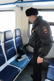 A police officer checks left things in the car commuter trains. MOSCOW, RUSSIA - JANUARY 29, 2014: A police officer checks left things in the car commuter Stock Photo