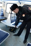 A police officer checks left things in the car commuter trains. MOSCOW, RUSSIA - JANUARY 29, 2014: A police officer checks left things in the car commuter Stock Photography