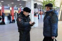 A police officer checks the national database informacionnoi at the entrance to Paveletskaya station. Stock Photos