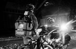 Police officer closing street Foodora food delivery waiting. Strasbourg, France - Oct 27, 2018: Police officer blocking the street - Foodora cyclist delivering stock photo