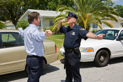 Police Officer Demonstrates. Police officer demonstrating a field sobriety test to a motorist Stock Image
