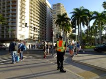 Police Officer Direct Traffic in Waikiki. Honolulu -  March 8, 2017: Police Officer Direct Traffic in front of Trump hotel on International Women's Day, in Royalty Free Stock Photos