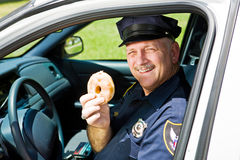 Police Officer and Doughnut. Police officer in his squad car holding a doughnut Royalty Free Stock Images