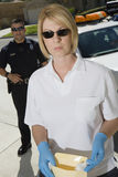 Police Officer With Evidence Envelope. Female police officer holding evidence envelope with coworker in the background royalty free stock photography