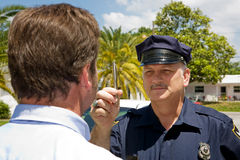 Police Officer - Eye Coordination. Police officer holding a pen and doing a field sobriety test on a motorist Stock Photo