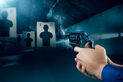 Police officer firing a gun at a shooting range / dramatic light Royalty Free Stock Image