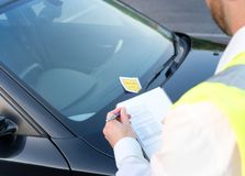Police officer giving a fine for parking violation. Police officer giving a ticket fine for parking violation Royalty Free Stock Photo