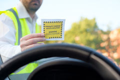 Police officer giving a  fine for parking violation. Police officer giving a ticket fine for parking violation Royalty Free Stock Images