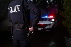 Police Officer grabbing his gun. A police officer standing near his car with the light on Stock Photo