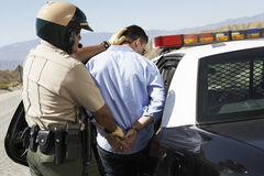 Police Officer Guiding Apprehended Man Into Police Car. Rear view of a police officer guiding apprehended men into police car Stock Image