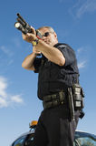 Police Officer With Gun. Low angle view of male police officer aiming with gun by patrol car Royalty Free Stock Image