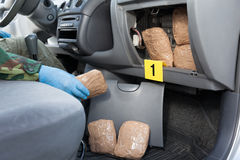 Police officer holding drug package found in secret compartment. Policeman holding drug package discovered in secret compartment in a car Stock Image
