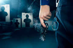 Police officer holding a gun at a shooting range / dramatic ligh Stock Photos