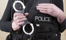 Police officer holding hand cuffs. Female police office holding a pair of rigid handcuffs Stock Photo