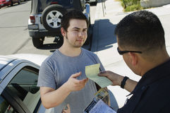 Police Officer Holding Out Ticket. Police officer giving ticket to young men for breaking traffic rules Stock Photos
