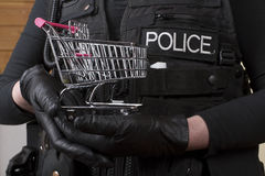 Police officer holding  small shopping trolley Stock Photography