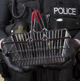 Police officer holding small wire basket