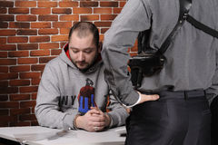 Police officer interrogates detainee Stock Photos