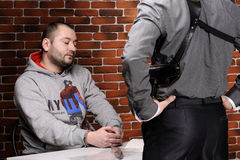 Police officer interrogates detainee Stock Photo