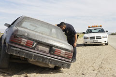 Police Officer Looking Into Abandoned Car Stock Photo
