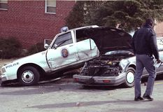A police officer looks at a auto accident involving a police car. In Capital Heights, Maryland royalty free stock image