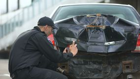 Police officer making photos of crashed car after road accident, filling report. Stock footage stock video footage