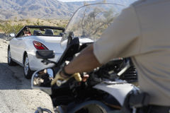 Police Officer On Motorbike Stopping Car On Desert Road. Cropped police officer on a motorbike stopping car on the desert road Stock Photo