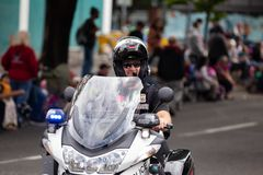 Police officer on motorcycle driving down the street. Portland, OR / USA - June 11 2016: Grand floral parade. Police officer on motorcycle driving down the stock photography