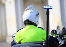 Police officer on motorcycle with flashing blue siren in the cit Royalty Free Stock Photography